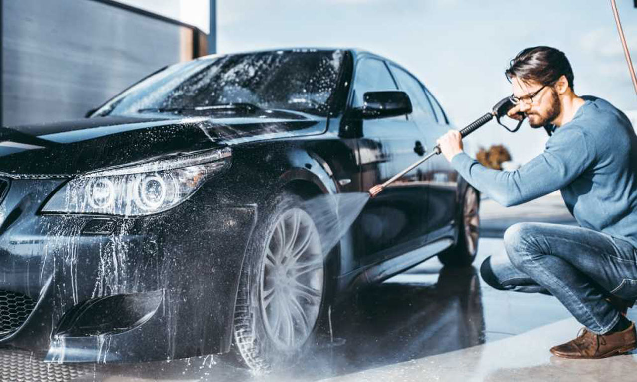 A man using a high pressure car wash facility to clean his wheels.