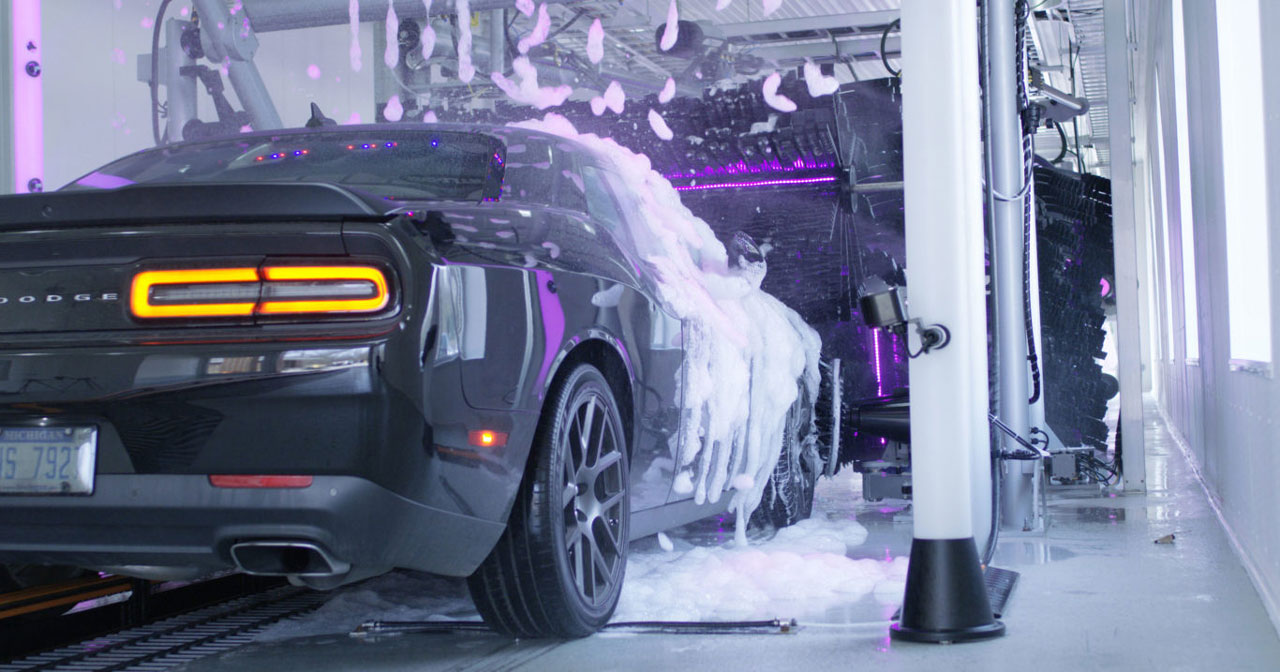 A purple dodge going through a hybrid car wash