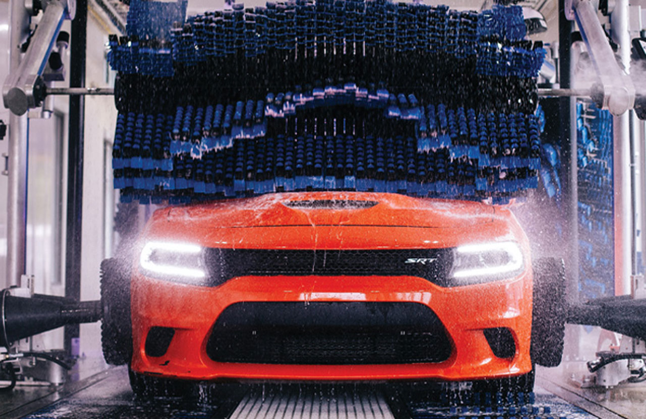 An orange dodge getting scratched at an automatic car wash