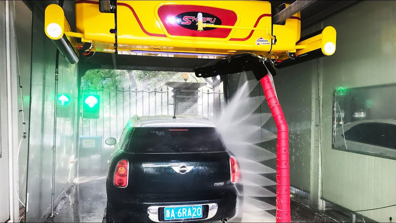 A fiat being washed in an automatic car wash that is touchless.