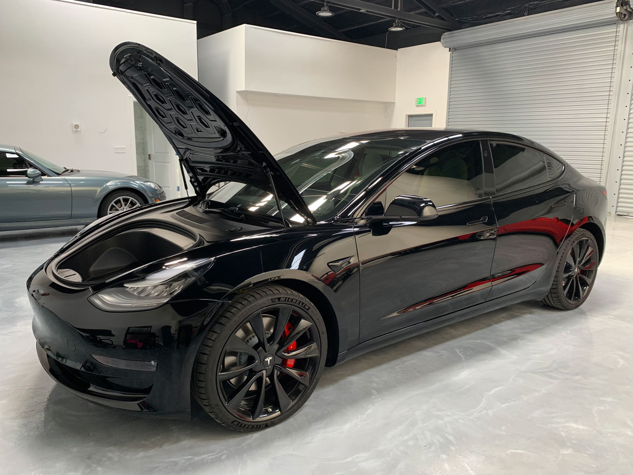 A black Tesla with a ceramic coating applied.